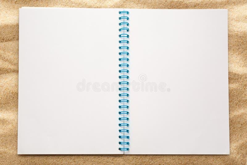 Anule o bloco de notas aberto na areia foto de stock