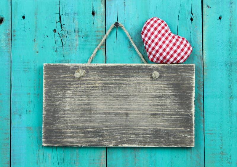 Anule o sinal de madeira afligido com o coração quadriculado vermelho que pendura na porta antiga rústica do azul da cerceta