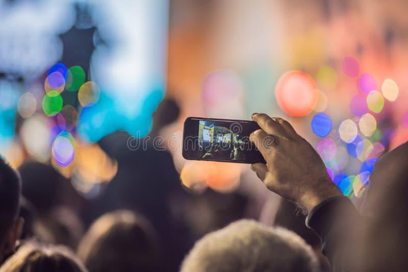 Använd avancerad mobil inspelning, roliga konserter, och härlig belysning, den franka bilden av folkmassan på vaggar konsert, stä royaltyfria bilder