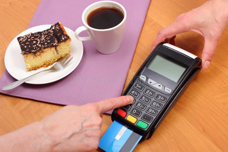 Använd betalningterminalen för att betala för ostkaka och kaffe i kafét, finansbegrepp arkivbilder