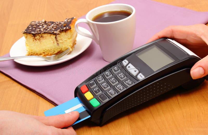 Använd betalningterminalen för att betala för ostkaka och kaffe i kafét, finansbegrepp royaltyfri foto
