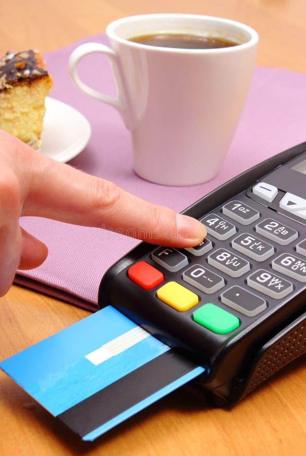 Använd betalningterminalen för att betala för ostkaka och kaffe i kafét, finansbegrepp fotografering för bildbyråer