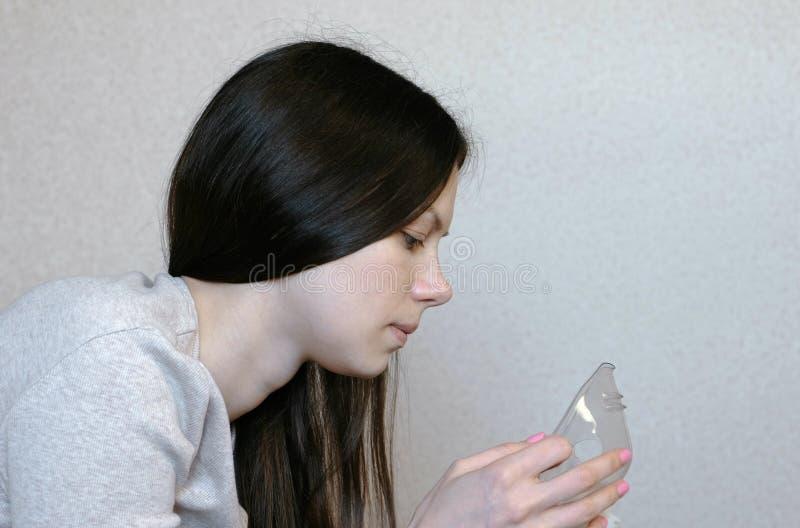 Använd nebulizeren och inhalatorn för behandlingen Den unga kvinnan förbereder inhalation till och med inhalatormaskering closeup arkivfoton