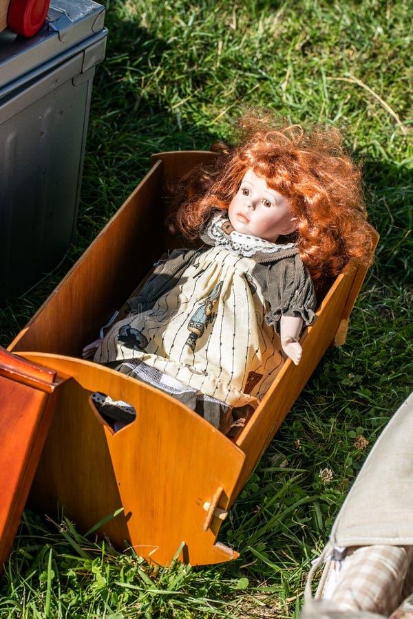Använd röd-hår docka i trävagga på välgörenhetförsäljningen royaltyfria bilder