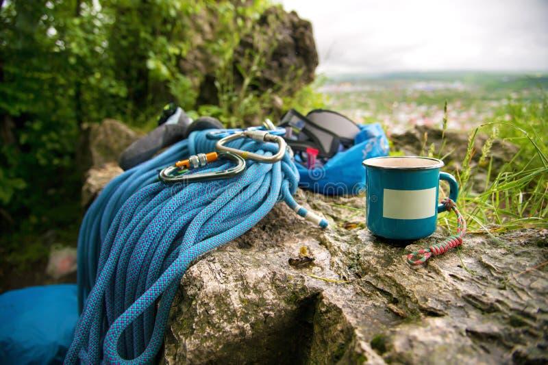 Använd utrustning för att klättra var repcarabinersna och klättringhäftklammermatarna bredvid råna på som en tom platta royaltyfri foto