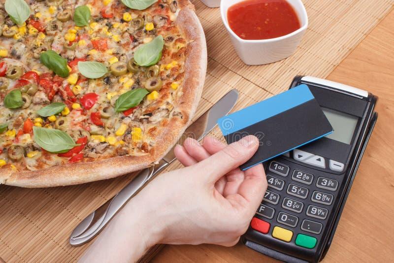 Använda betalningterminalen med den contactless kreditkorten för att betala i restaurang, finansbegrepp, vegetarisk pizza arkivbild