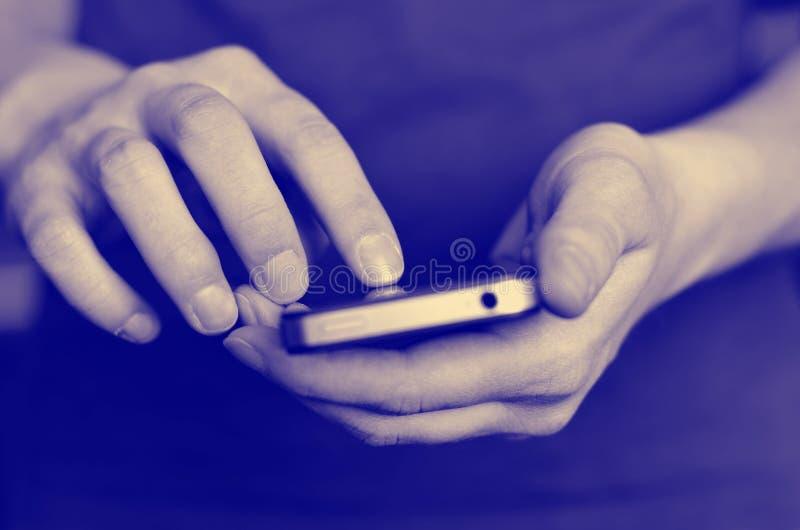 Använda den smarta telefonen för att meddela text arkivbild