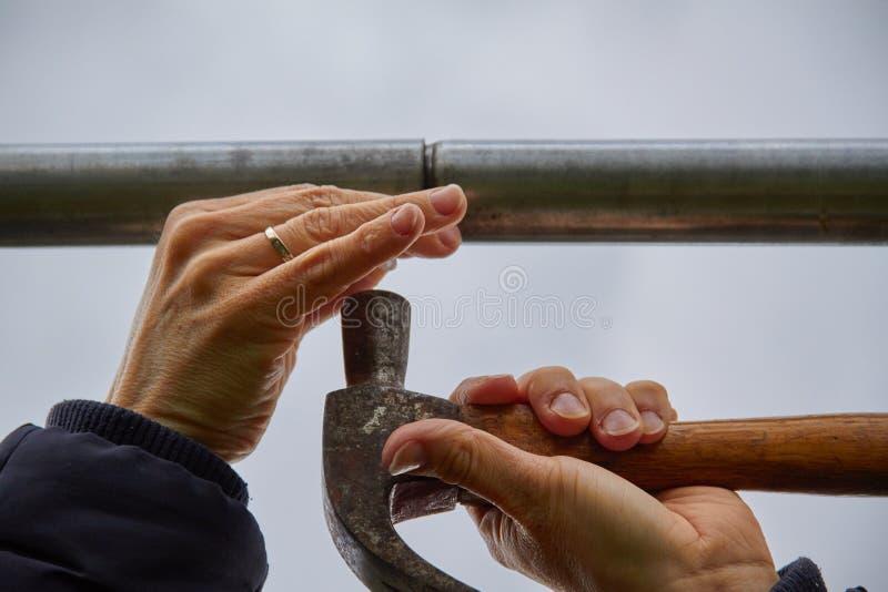 Använda en hammare med women& x27; s-händer som spikar en aluminiumstång Gr? himmelbakgrund fotografering för bildbyråer