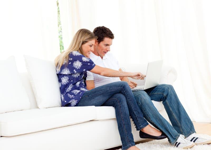 använda för sofa för parbärbar dator glatt sittande fotografering för bildbyråer