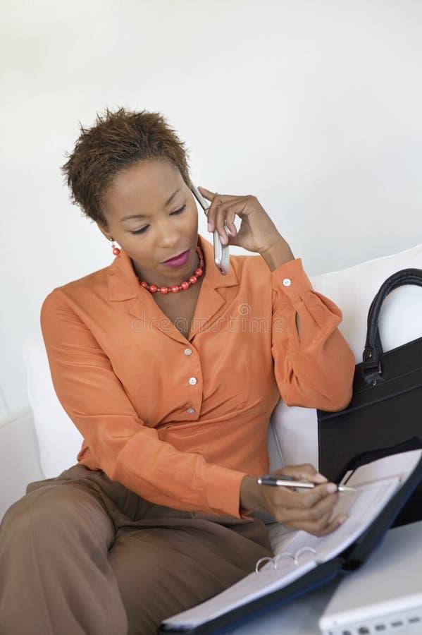 använda för telefon för affärskvinnacellorganisatör arkivfoto