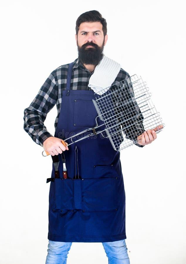 Använda köksgeråd för förberedande och tjänande som mat Skäggig man som rymmer bbq-korgen och redskap Gallerkock med raster royaltyfri fotografi