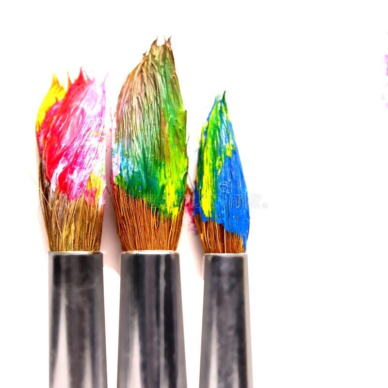 Använda målarfärgborstar av olika färger, på en vit bakgrund arkivbild