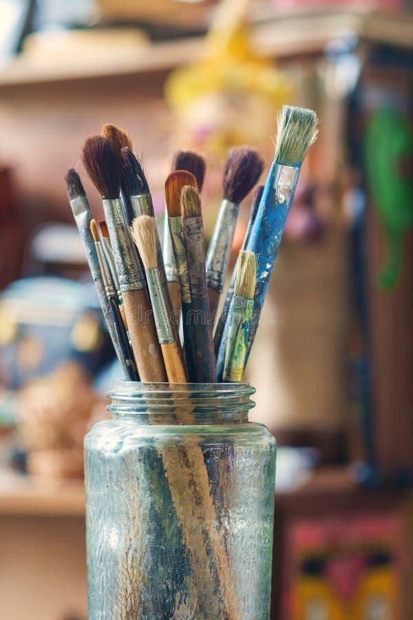 Använda målarfärgborstar i exponeringsglaskruset royaltyfria foton