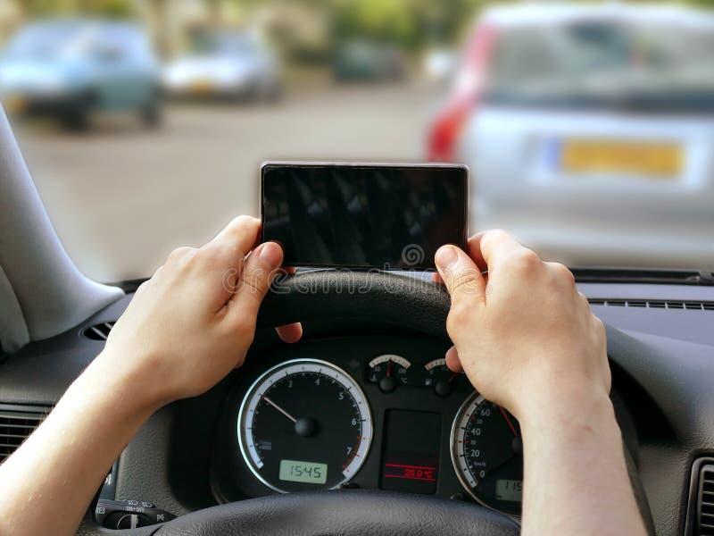 Använda mobiltelefonen, medan köra Farligt körande begrepp royaltyfria foton
