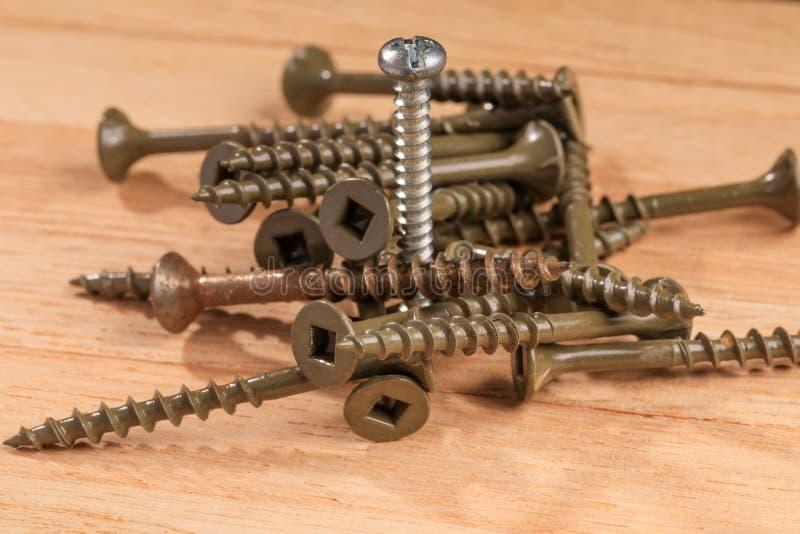 Använda skruvar för konstruktionsprojekt på en träbrädebakgrund royaltyfri bild