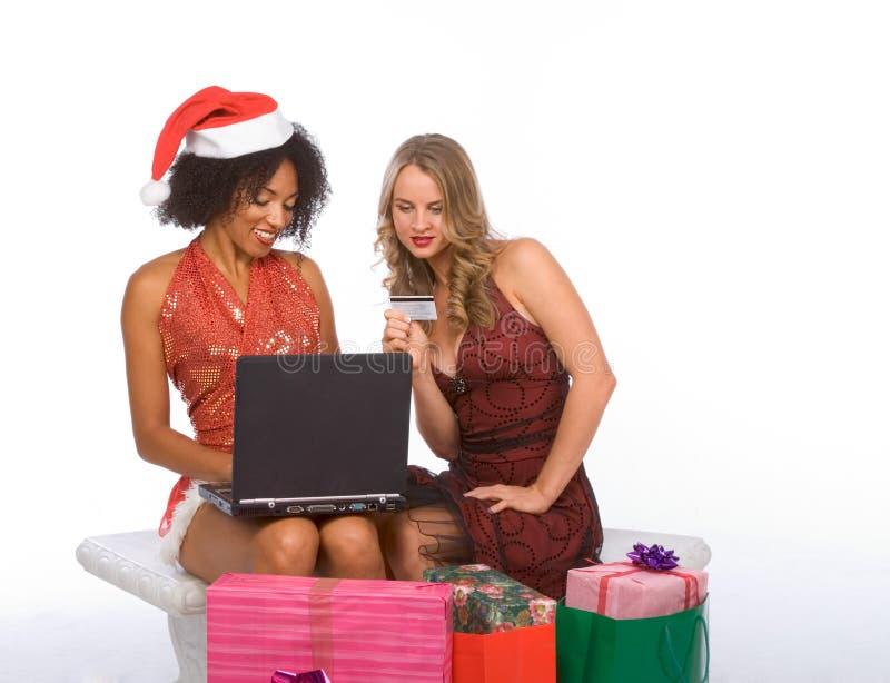 användande kvinnor för julbärbar datoronline-shopping två royaltyfria bilder