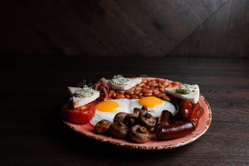 Användbar engelsk frukost med stekte ägg med champinjoner och korvar med saftig bacon med rostat bröd och inlagda bönor i tomatså royaltyfria bilder