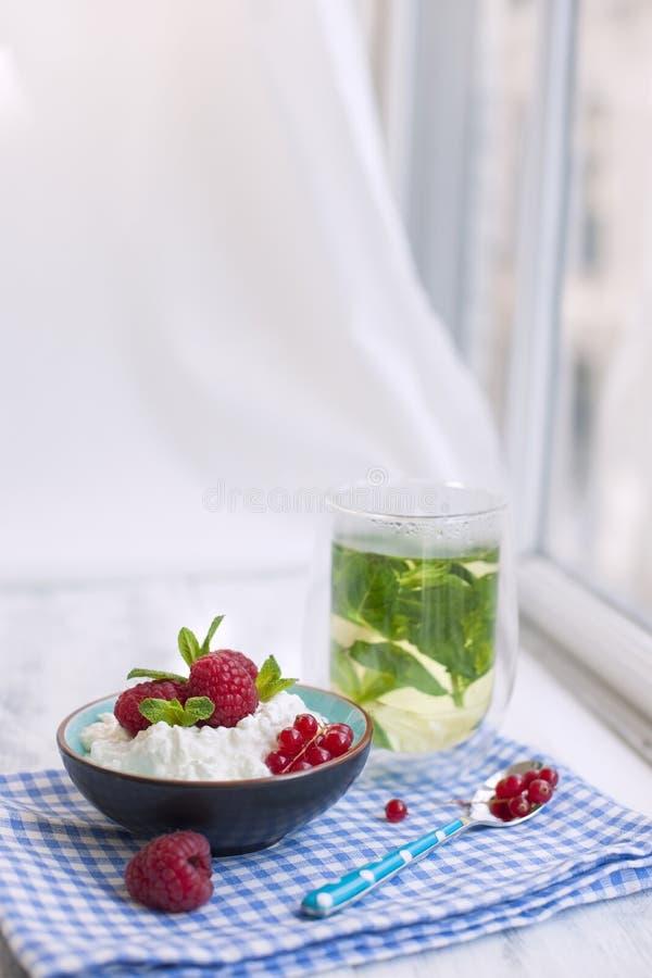 Användbar frukost av mysli och yoghurten med bär i ett exponeringsglas glass tea En bukett av blommor i en blå vas Vår royaltyfria bilder