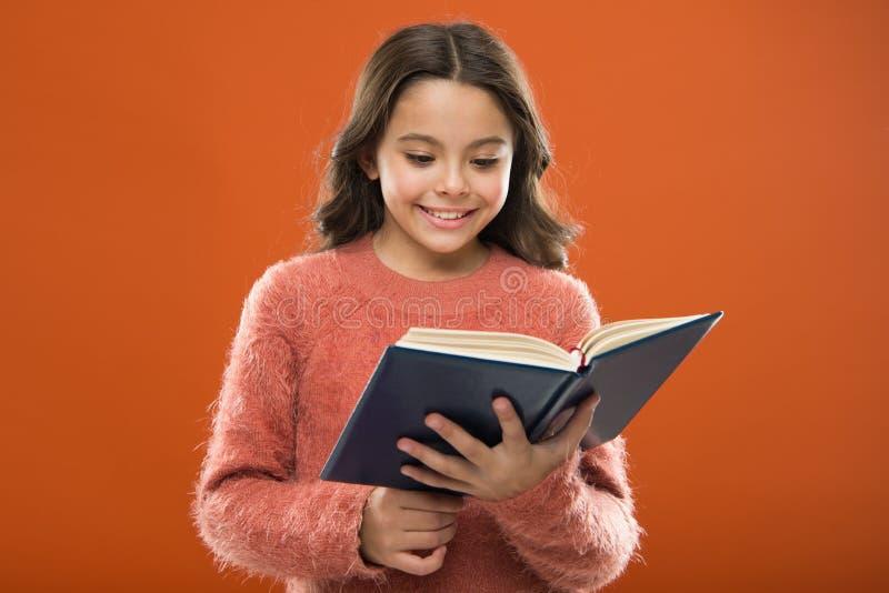 Användbar information för henne Flickahållboken läste berättelse över orange bakgrund Barnet tycker om läseboken Boklager royaltyfria foton