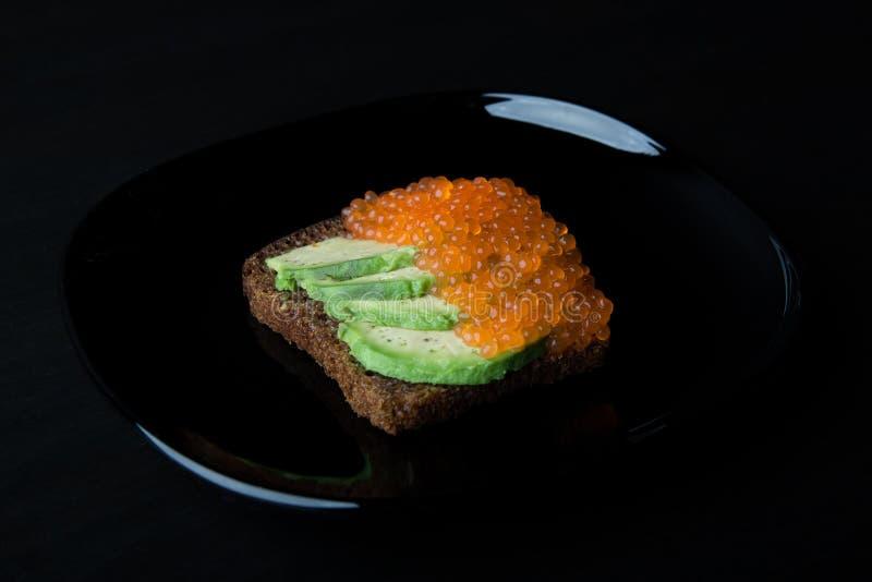 Användbar smörgås från svart bröd, den mogna avokadot och den röda kaviaren royaltyfria bilder