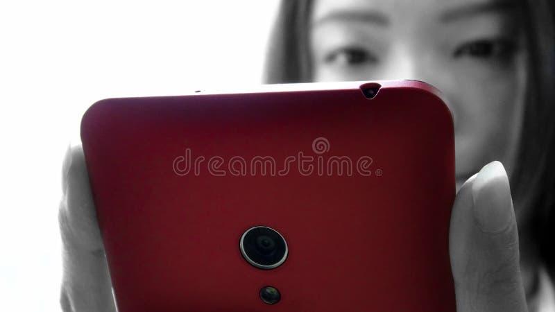 Använde den asiatiska kvinnan för closeupen minnestavlasmartphoneapparaten arkivbild