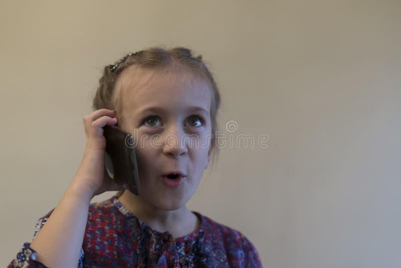 använder årig flicka 5 en smartphone talar på mobiltelefonen och le Flicka som talar på smartphonen Liten unge arkivbilder