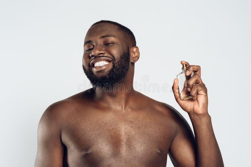 Använder den stiliga mannen för afrikanska amerikanen eau-de-cologne royaltyfri bild