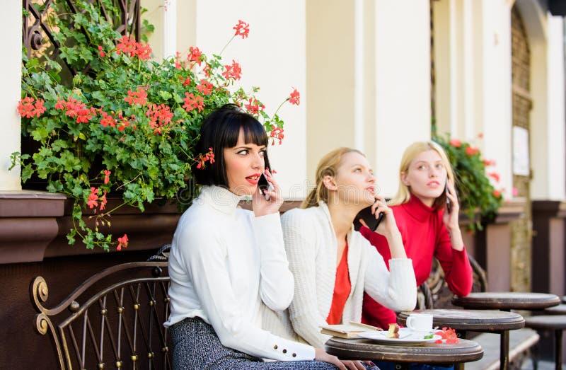 Anv?nda digitala apparater Terrass för gruppkvinnakafé Kamratskapm?te Mobilen missbrukade Mobil konversation Flickor med arkivfoton