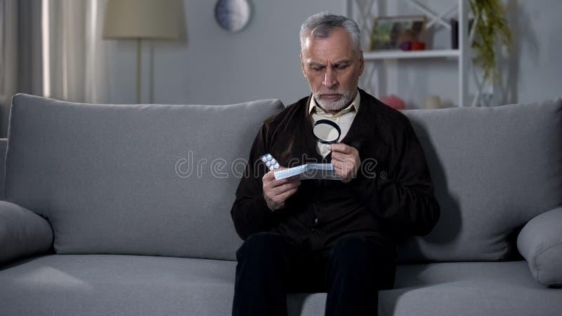 Anweisung des alten Mannes Lesefür Pillen mit Vergrößerungsglas, Visionsbeeinträchtigung behandelnd lizenzfreies stockfoto