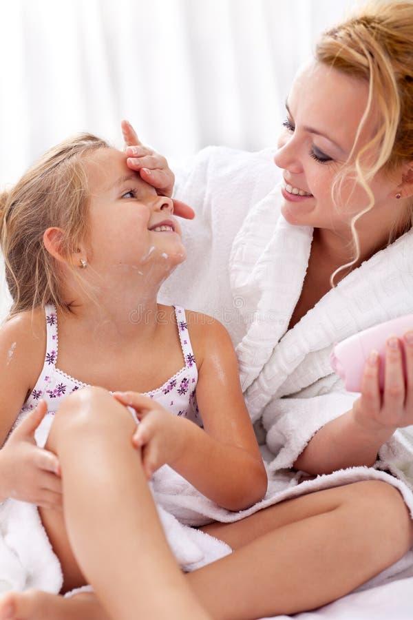 Anwenden der Gesichtssahne und der Karosserienlotion stockfotos