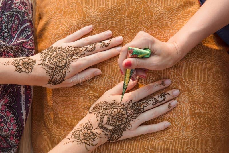 Anwenden der Hennastrauchtätowierung auf Frauenhänden stockfoto