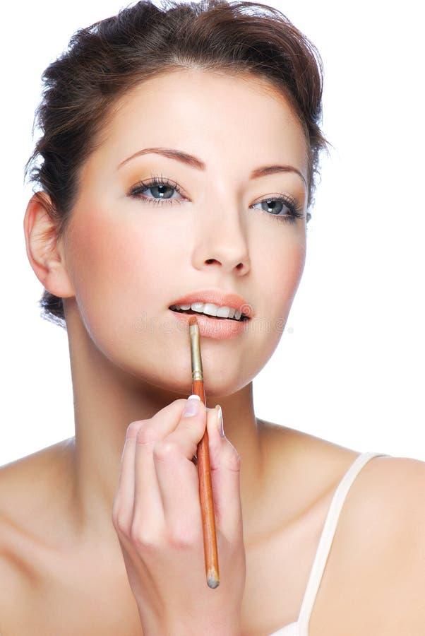 Anwenden des Lippenstifts unter Verwendung des Lippenconcealer Pinsels stockfoto