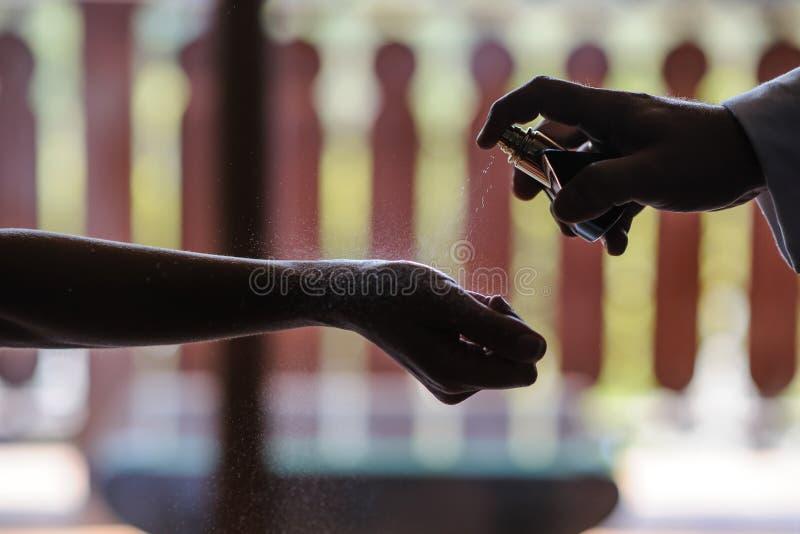 Anwenden des Parfüms auf schönem Handgelenk der jungen Frau lizenzfreies stockfoto