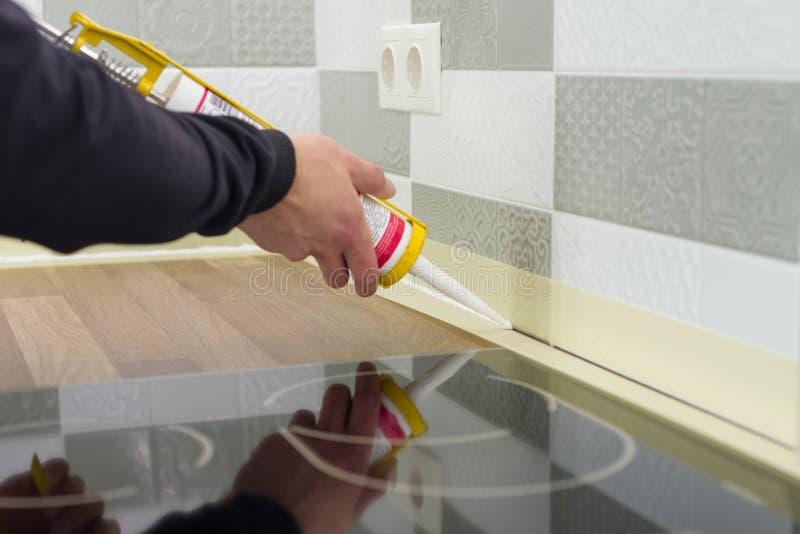 Anwenden des Silikondichtungsmittels mit Bauspritze Arbeitskraft füllt Naht zwischen den Keramikfliesen auf der Wand und Küche wo lizenzfreie stockfotografie