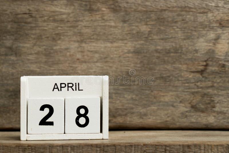 Anwesendes Datum 28 des weißen Kalenderblocks und Monat April auf hölzernem Hintergrund stockfoto