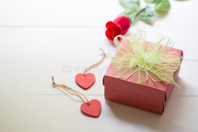 Anwesendes Geschenk mit roter rosafarbener Blume und Geschenkbox mit Bogenband- und -holzherzform auf Holztisch stockfotografie
