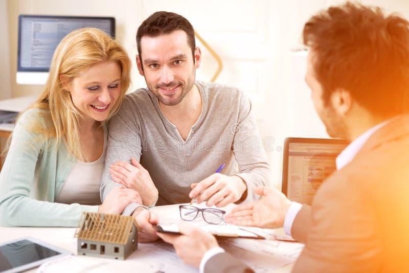 Anwesendes Projekt der Immobilienagentur auf Tablette zu einem jungen Paar lizenzfreies stockbild