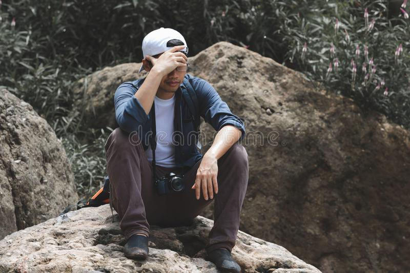 Anxiety stressed young Asian tourist man suffering from severe depression in nature royalty free stock images