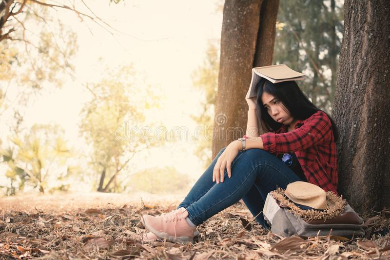 Anxiety woman about her studying sitting lonely under the big tree on park. Color of vintage tone and soft focus stock image