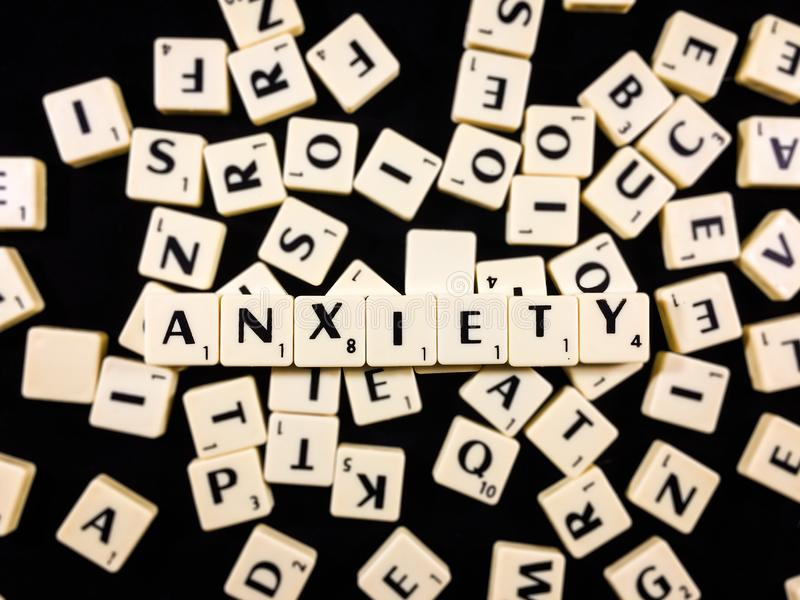 Anxiety word spelled with letter tiles in black background royalty free stock photography