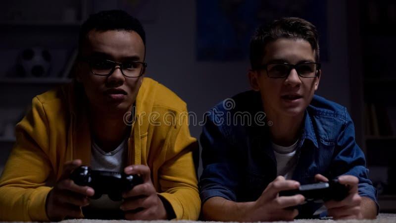 Anxious african-american and caucasian guys playing video game, procrastinators. Stock photo stock photo