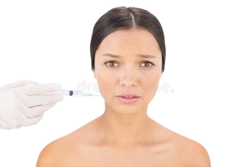 Anxious bare model having botox injection around mouth royalty free stock photos
