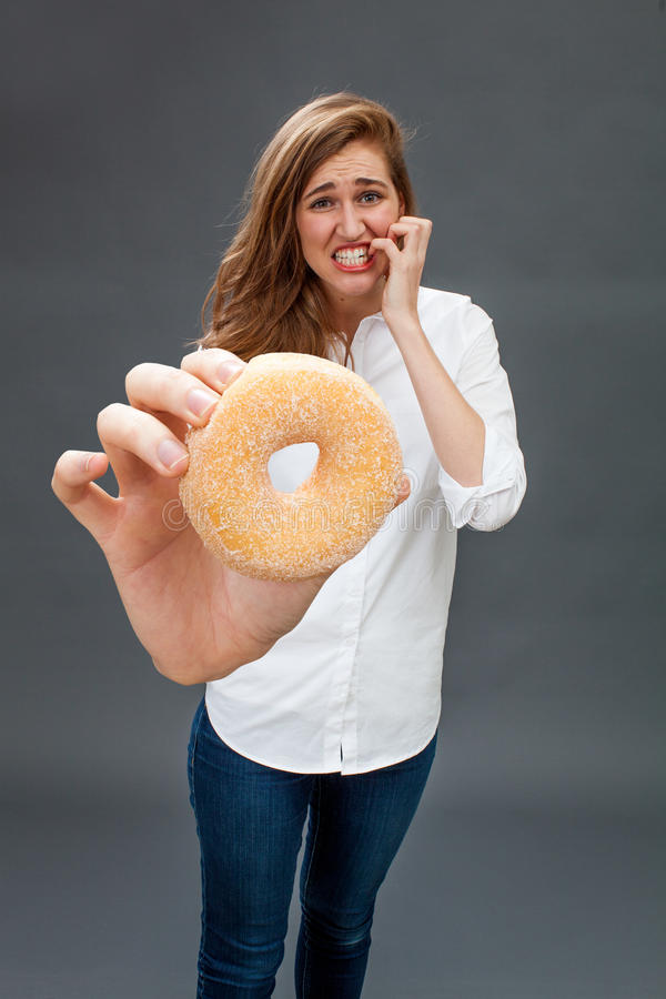 Anxious beautiful young woman biting her fingers for snacking danger stock photos