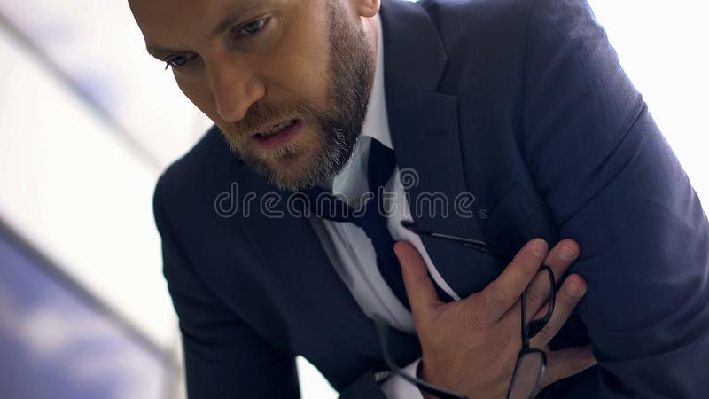 Anxious business man feeling chest pain, overworked manager, heart attack. Stock photo stock photography