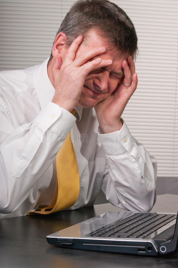 Anxious business man holds head. Despairing businessman at laptop and holds head as frustrated and unhappy about news or difficulty. Suffers headache stock photos