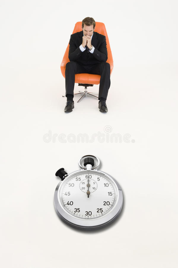 Anxious businessman sitting on chair with stopwatch in front of him representing loss of time stock photo