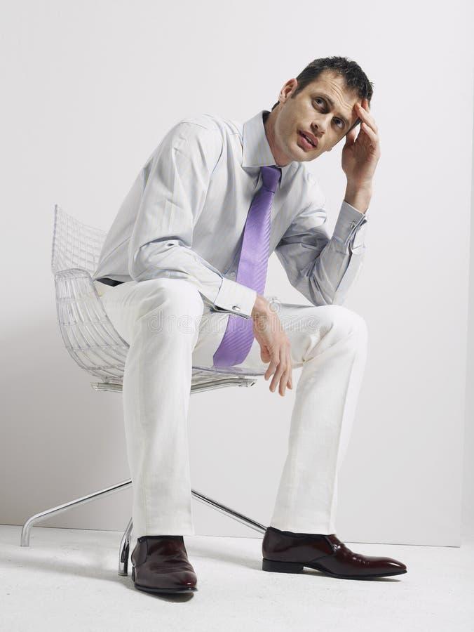 Anxious Businessman Sitting In Swivel Chair stock photo