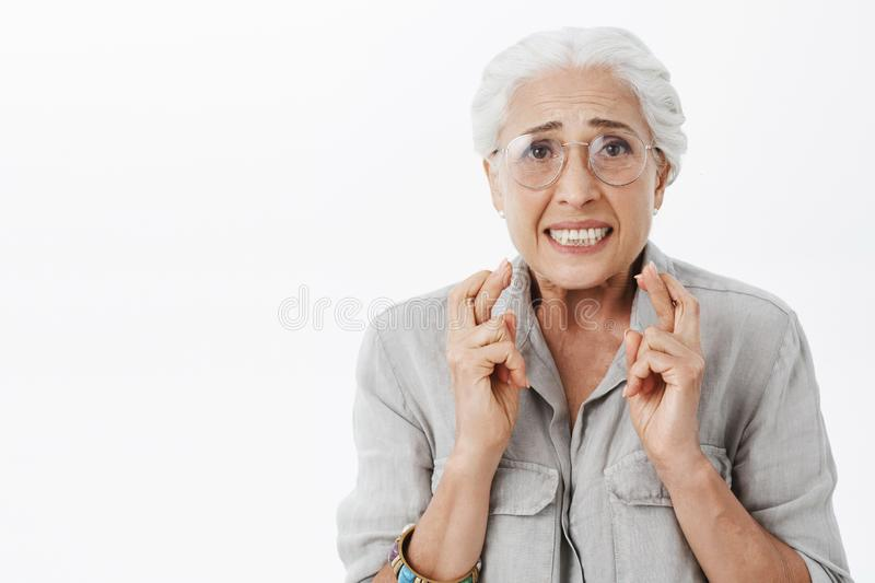 Anxious and concerned hopeful silly senior woman in glasses with white hair crossing fingers for good luck frowning stock photography