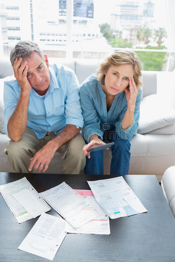 Anxious couple sitting on their couch paying their bills. Looking at camera at home in the living room stock photography
