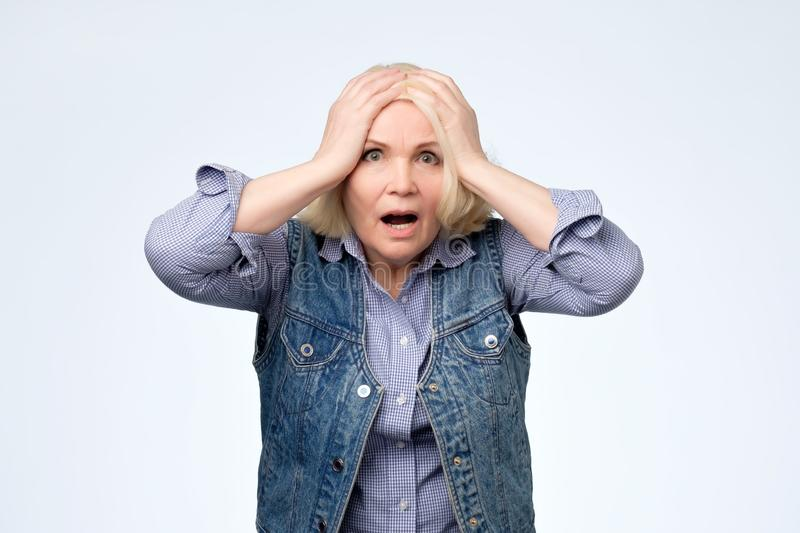 Anxious elderly blonde woman having frustrated stressed expression royalty free stock photo